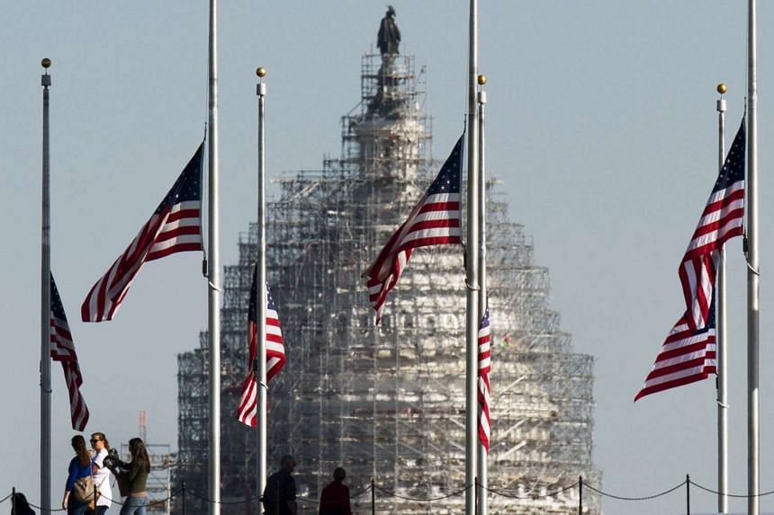 American flags surrounding the Washington Monument standing at half mast on Nov 16 in honour of the Paris attack victims.