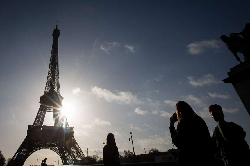 Tourists taking photographs of the Eiffel Tower in Paris on Nov 15.