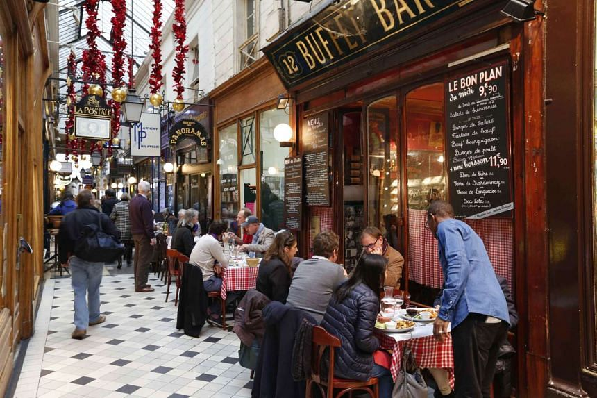 People sit in tables outside bistros in the Passage des Panoramas in Paris.