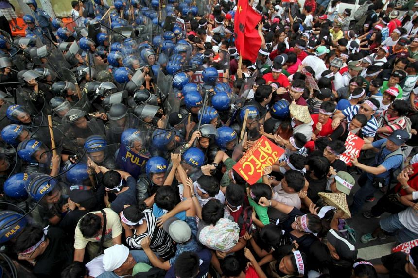 Protesters scuffle with the police near the venue of the Manila Apec summit.
