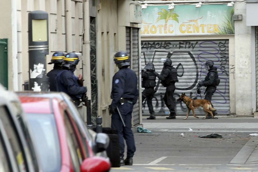 Members of special French RAID forces with a police dog during an operation in Saint-Denis, near Paris on Nov 18. 2015.