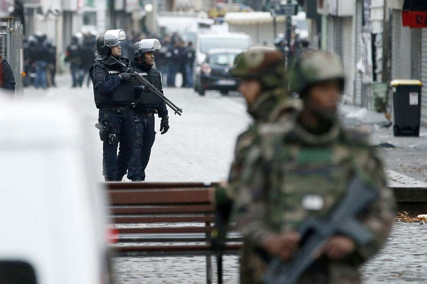 French military officers and police stand guard near the site were a raid happened in the city center of Saint Denis.