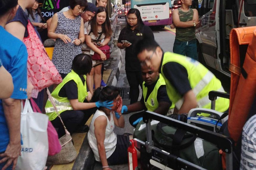 The woman being attended to by SCDF personnel.
