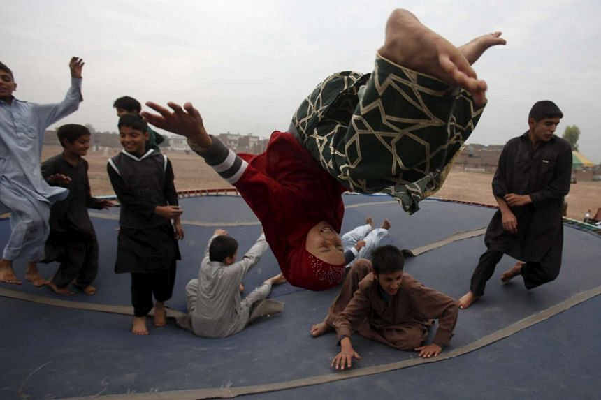 Children play on a trampoline at a playground on the outskirts of Peshawar, Pakistan.