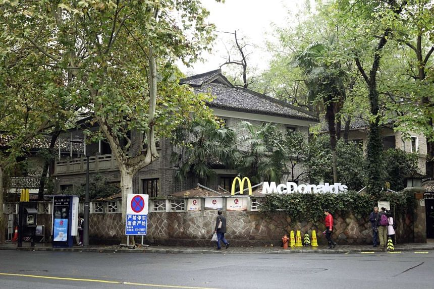 This picture taken on November 17, 2015 shows people walking past a McCafe near the famed West Lake tourist spot in the former home of late Taiwanese President Chiang Ching-kuo in Hangzhou, east China's Zhejiang province. A branch of Mcdonald's opene