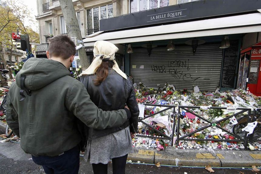 A couple standing in front of the La Belle Equipe cafe, one of the sites of the attacks in Paris, on Nov 17.