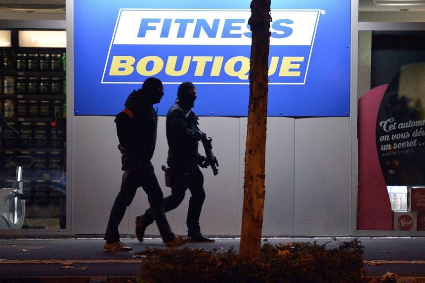 Policemen walking along a building in Strasbourg on Nov 16, during investigations following the Nov 13 attacks in Paris.