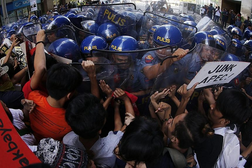 Protesters clashing with riot police during a rally in Manila yesterday against the two-day Apec summit, which begins today.