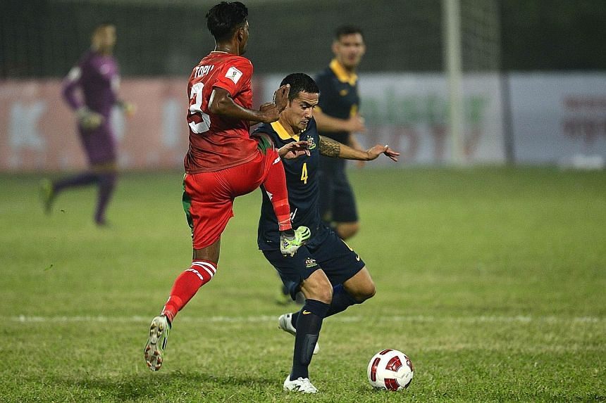 Australia's Tim Cahill (right) vying for the ball with Bangladesh's Topu Barman during their Asian Group B World Cup qualifier in Dhaka yesterday. The veteran forward scored his second international hat-trick as Australia set aside security worries t