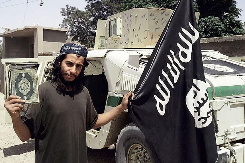 A picture from the February issue of ISIS' Dabiq magazine, purportedly showing Abdelhamid Abaaoud, the man suspected of orchestrating the attacks in Paris last Friday that left at least 129 people dead. French President Francois Hollande with United