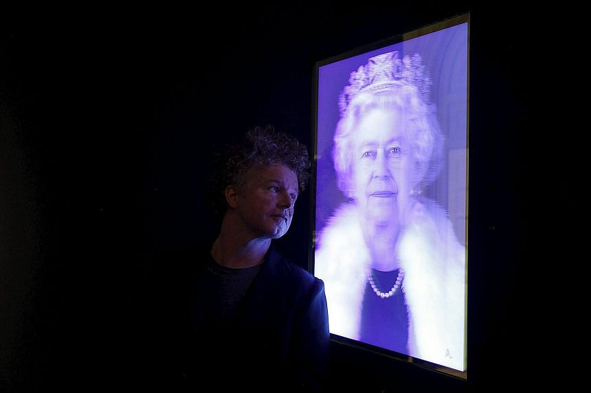 Artist Chris Levine posing with his lenticular image of Britain's Queen Elizabeth II at the National Portrait Gallery in London.
