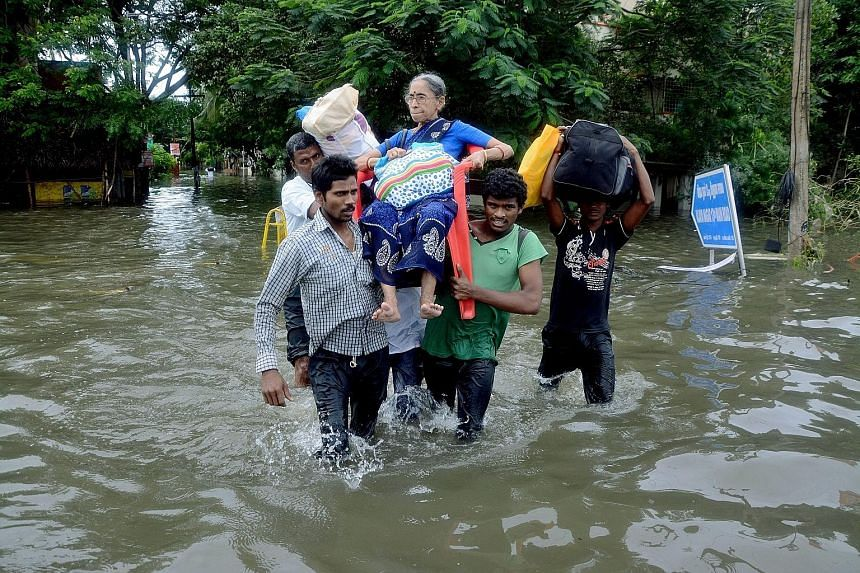 Residents carrying an elderly woman who was trapped in her home due to flooding in Chennai on Monday. India's annual monsoon season lasts from June to September.