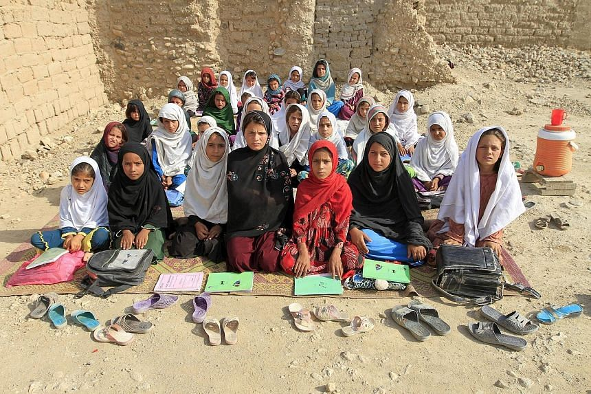 Teacher Mahajera Armani and her class of girls at their open study area, founded by the Bangladesh Rural Advancement Committee, outside Jalalabad, in Afghanistan.