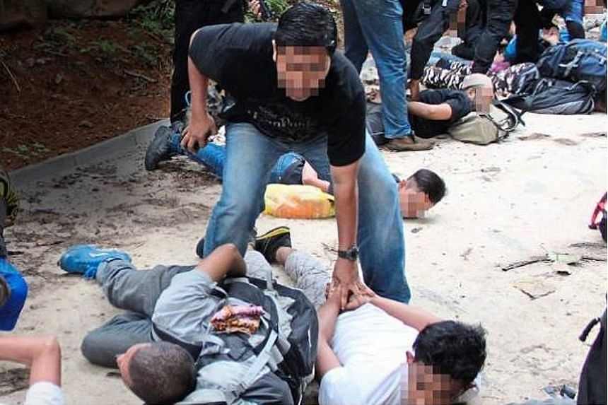 Officers from Malaysia's Bukit Aman Special Branch Counter Terrorism Division detaining suspects at the foothills of Hutan Lipur Gunung Nuang in April. The men, suspected ISIS militants, were testing bombs at the foothills of the mountain when they w
