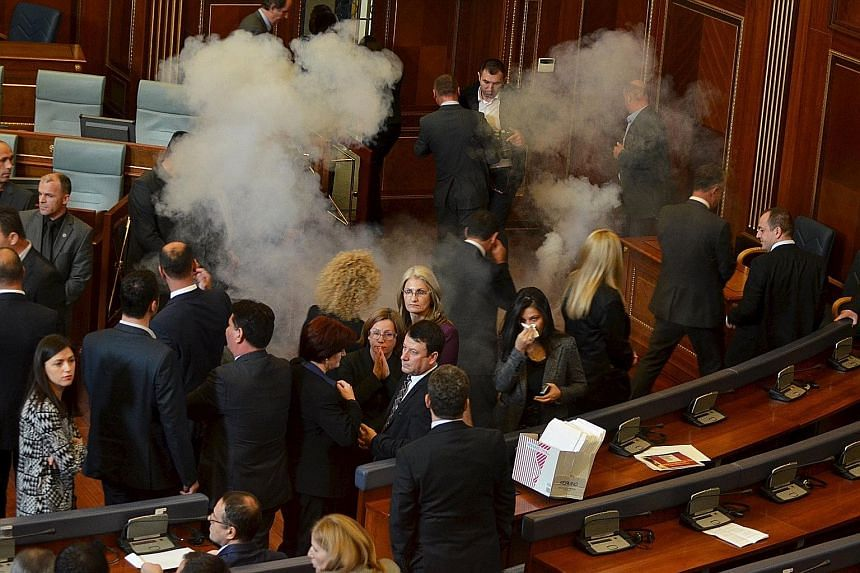 Kosovo MPs in Parliament yesterday when opposition lawmakers protesting against deals with Serbia fired tear gas and pepper spray.