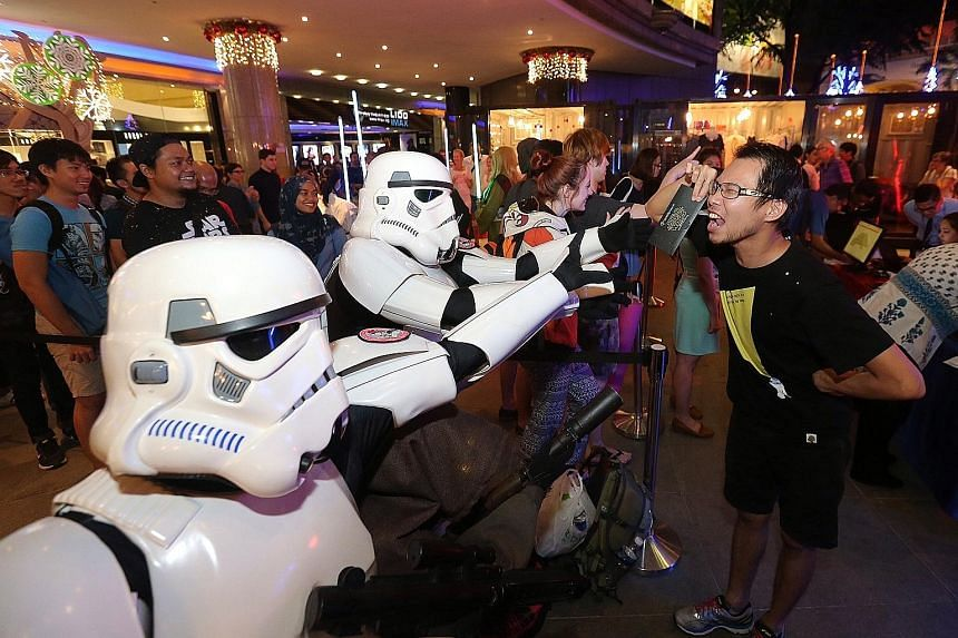 Fans dressed as Star Wars villains Stormtroopers playfully trying to snatch tickets from Mr Nicholas Ho (right).