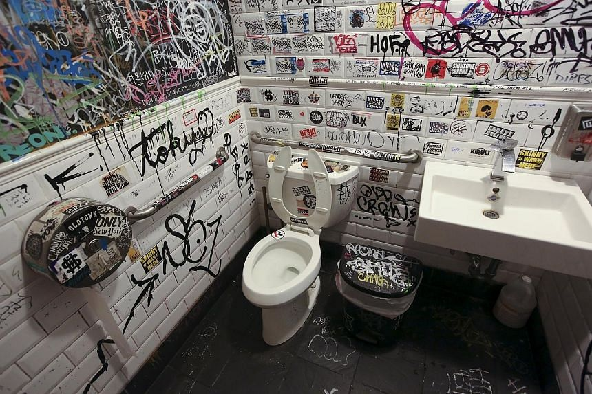 A restaurant toilet with graffiti-covered walls in Brooklyn, New York (top), and the entrance to a public toilet with escalator ramps in Istanbul, Turkey (above).