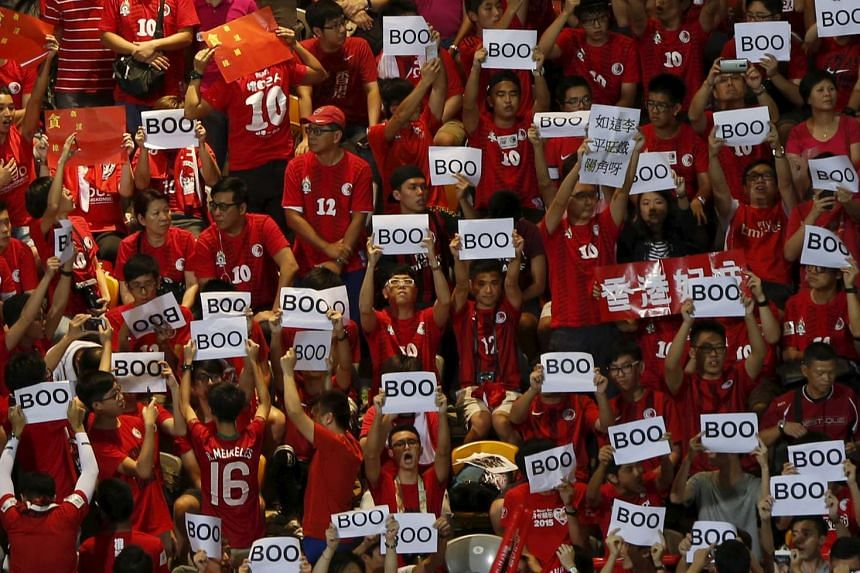 """Hong Kong fans hold """"boo"""" signs, during the Chinese national anthem."""