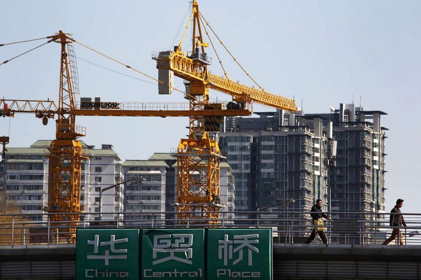 Pedestrians walk past cranes and residential buildings under construction in Beijing, China.