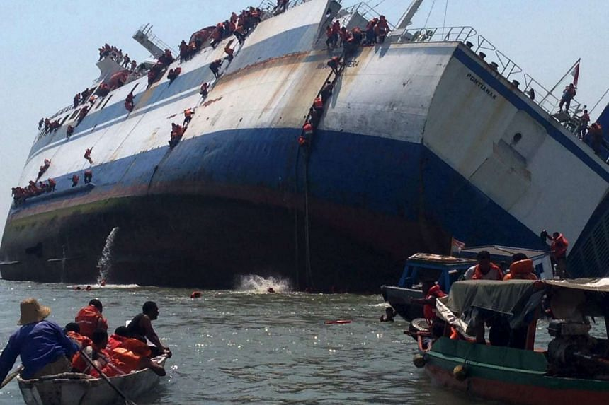 Passengers climb down the side of the ferry KM Wihan Sejahtera as it capsizes in Tanjung Perak port on Nov 16, 2015.