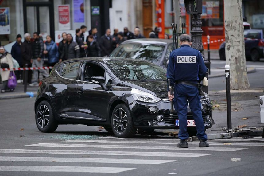 A French police officer stands near a suspected car which was used during the attacks in Paris on Nov 13, 2015.