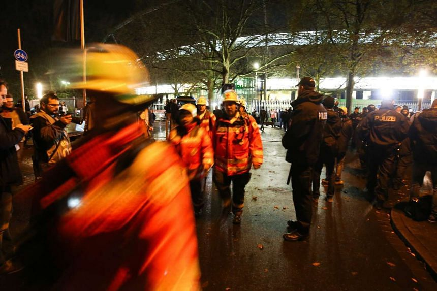 Police and firemen in front of the HDI-Arena stadium in Hanover, Germany,