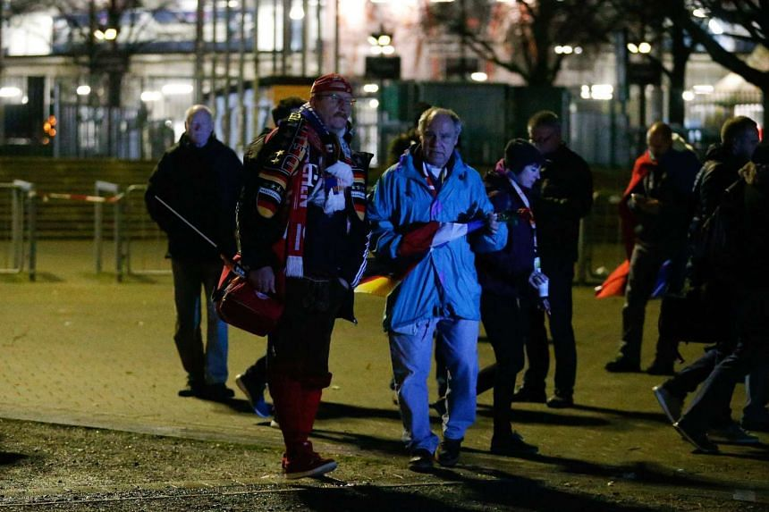 Supporters leave the stadium after the match was called off by police.