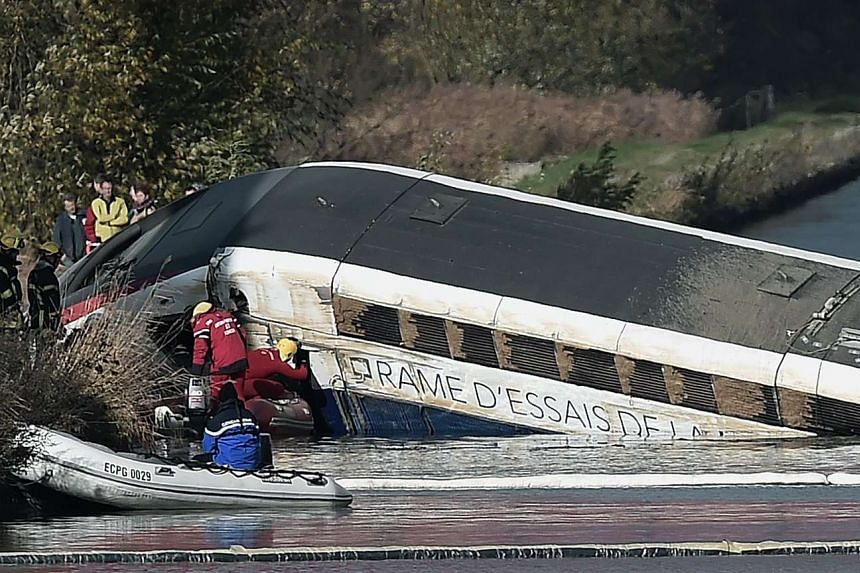 Emergency personnel working at an accident scene where a high-speed TGV train coach and engine carriage derailed, near Strasbourg, on Nov 15, 2015.