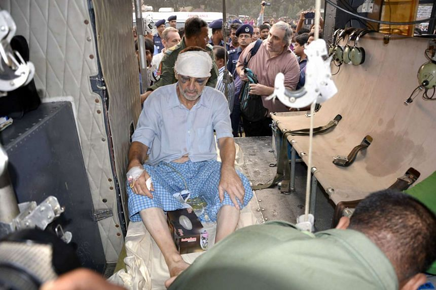 An Italian priest sits wounded as he is treated after being shot in Dinajpur.