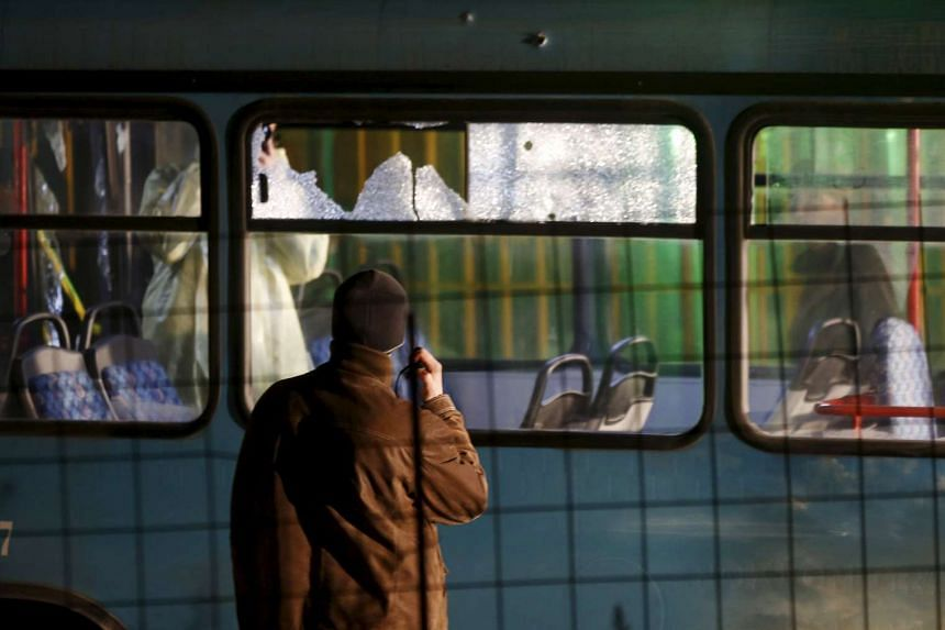 Forensic personnel investigate a bus with windows broken by bullets after an attack in Sarajevo on Nov 19, 2015.
