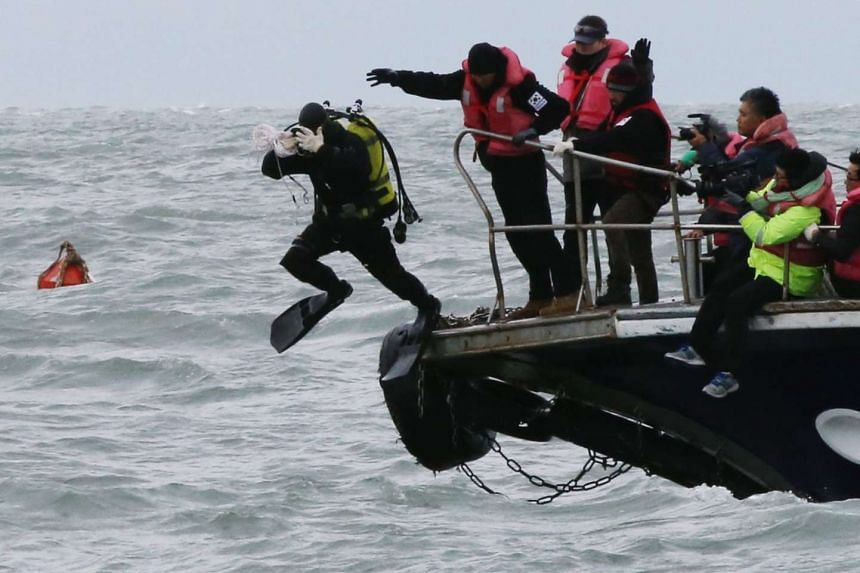A diver jumping into the water to inspect the sunken ferry Sewol as part of a probe.