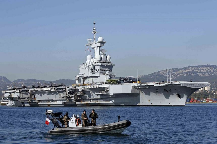 French army soldiers secure the area around the nuclear-powered aircraft carrier Charles de Gaulle as it leaves the naval base of Toulon, France on Nov 18, 2015.