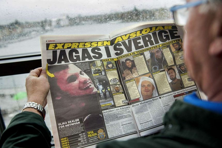 A man reading a newspaper displaying a grainy photograph of a man believed to be suspected of planning terror crimes in Sweden, in Stockholm on Nov 19, 2015.