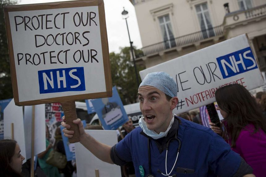 A protester holds a placard at a demonstration in support of junior doctors in London.