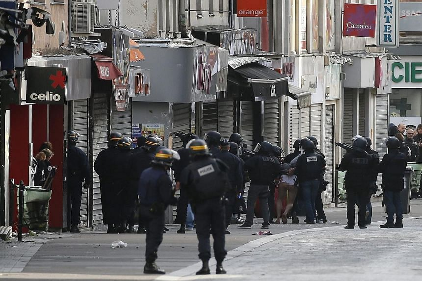 A man being arrested by police officers at the site where a raid took place in the northern Paris suburb of Saint-Denis yesterday. The raid came after footage from the scene of one of the Paris attacks revealed a ninth suspect may have taken part.