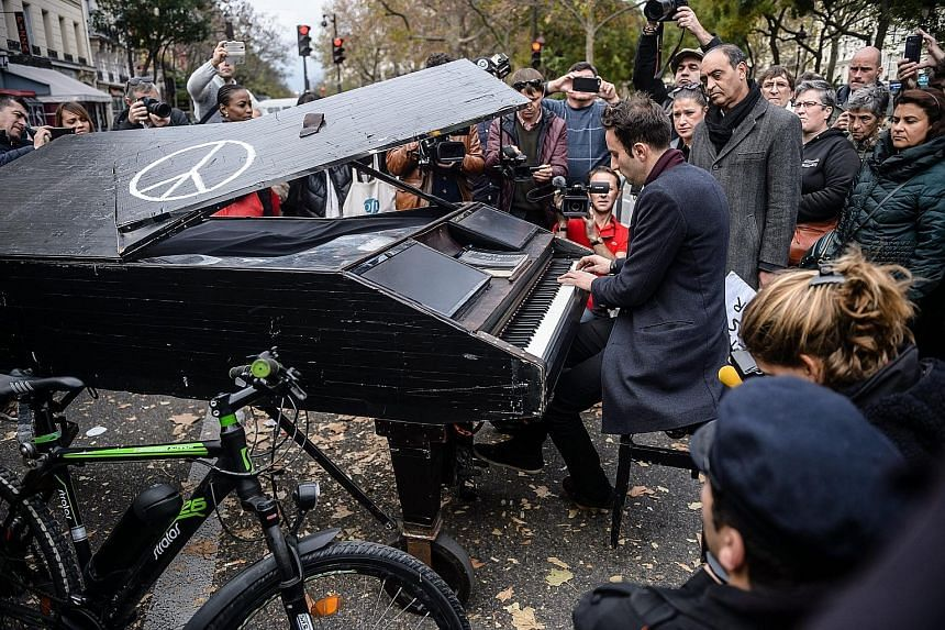 Musician Davide Martello playing John Lennon's Imagine near the Bataclan concert hall on Monday. After learning of the Paris attacks, he put his piano on a trailer and drove 640km from the south-western German city of Konstanz to Paris.