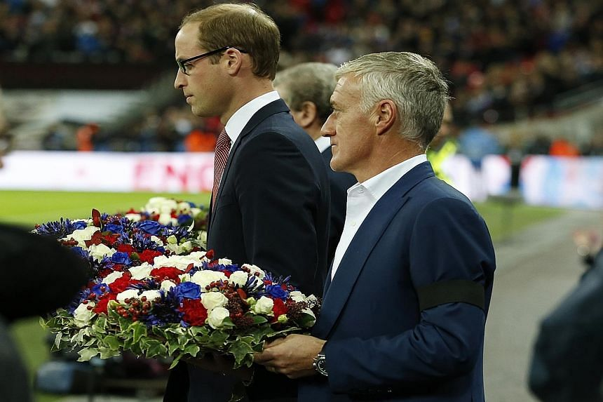 Britain's Prince William and France coach Didier Deschamps carrying floral tributes before the game, in memory of last Friday's Paris terrorist attacks.