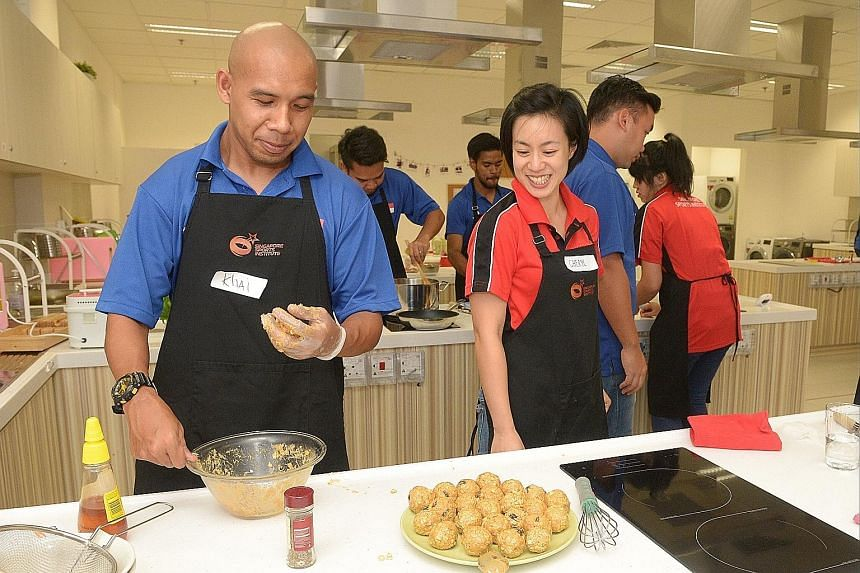 Singapore cerebral palsy football captain Khairul Anwar captain making muesli balls under the guidance of Singapore Sports Institute associate sport dietitian Cheryl Teo last night. The workshop was the second conducted on eating for recovery.