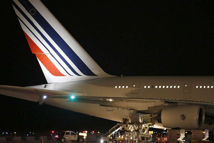 Workers load cargo on an Air France Airbus 380, Flight 65, on the runway at Salt Lake City International Airport after being inspected by the FBI on Nov 17, 2015 in Salt Lake City, Utah.