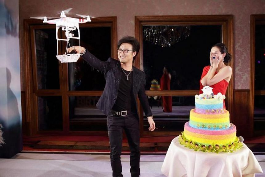 Wang Feng (left) reaching for the diamond ring carried by the drone.