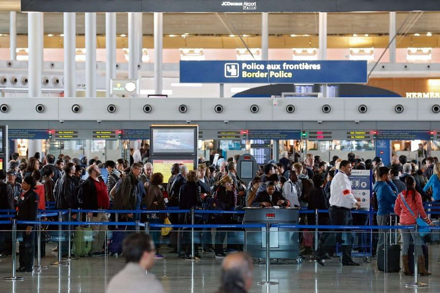 Passengers queue at the border police control inside the airport Charles de Gaulle in Paris, France, Nov 14, 2015.