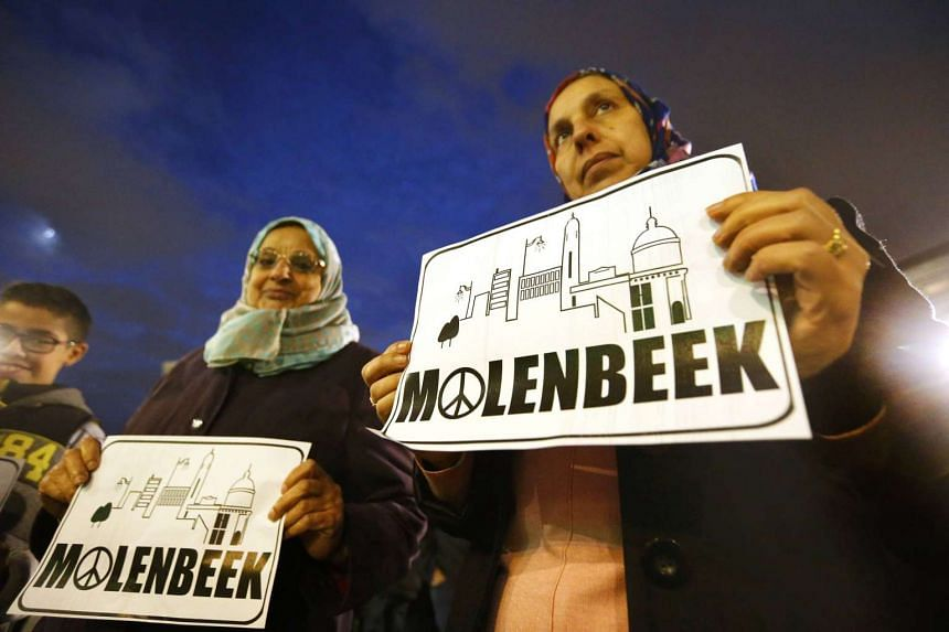 Residents of the Brussels suburb of Molenbeek take part in a memorial gathering to honour the Paris victims.