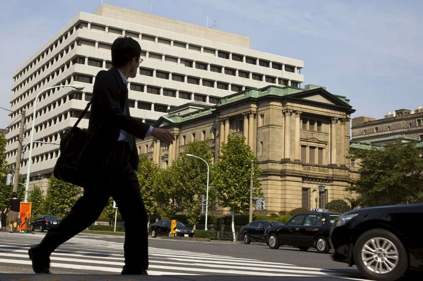 A man walks past the Bank of Japan (BOJ) building in Tokyo, Oct 30, 2015.