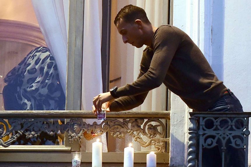 Mohamed Abdeslam, a brother of two men who helped carry out terrorist attacks in Paris, places candles on a window ledge of the family apartment.