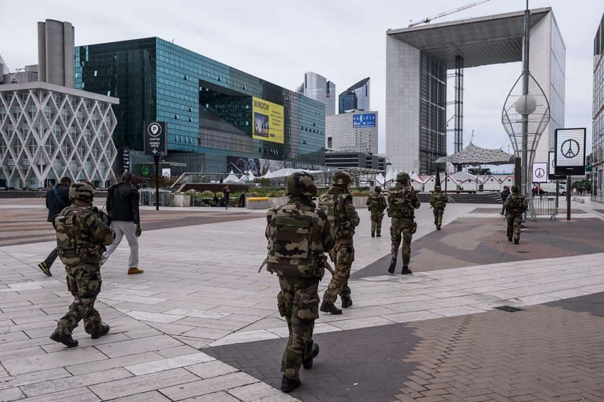 French soldiers patrol La Defense business district, with the Quatre Temps shopping centre (second left).