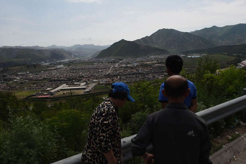 Chinese tourists looking across the border to the North Korean town of Musan.