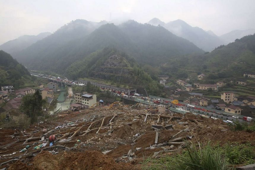 Rescuers working among debris at the landslide in Zhejiang province, China.
