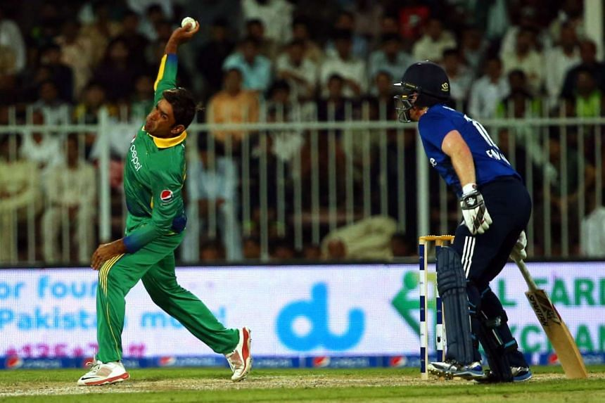 Pakistan's Iftikhar Ahmed delivers a ball as England's Eoin Morgan looks on during the third One Day International match between Pakistan and England at the Sharjah Cricket Stadium in the Gulf Emirate of Sharjah on Nov 17, 2015.