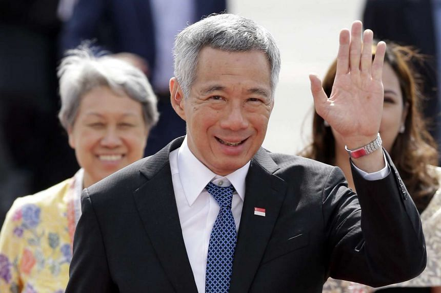 Singapore Prime Minister Lee Hsien Loong (center), with wife Ho Ching (left), waves upon his arrival at Manila's International airport prior to attend the APEC Summit in Manila, Philippines, Nov 18, 2015.