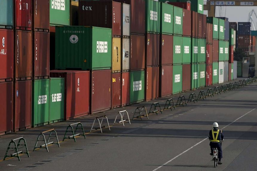 A worker rides a bicycle in a container area at a port in Tokyo, Japan, Oct 20, 2015.